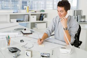 Architect on phone while writing on notepad